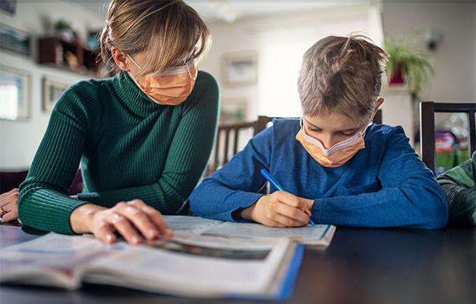 Woman helping child study, both wearing face masks