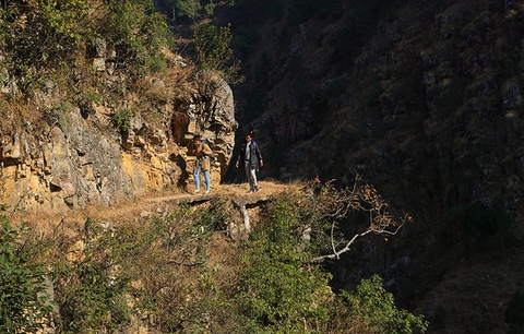 Ms. Bhandari and her colleague Kalawati trek along a steep cliff. They are travelling to rural villages as part of a UNFPA programme supported by the United Kingdom Department for International Development. © UNFPA Nepal