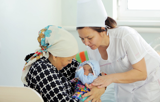 Midwife Venera Jumabayeva assists a new mother