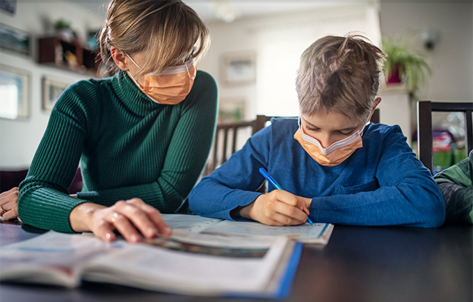 Woman helping child study, both wearing face masks