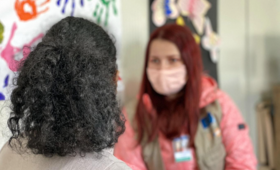 Two women talking together. One with her back to the camera, the other wearing a mask.