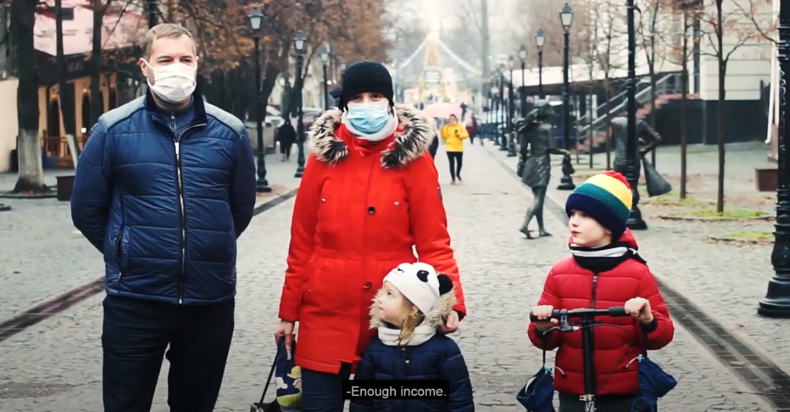 Mom, dad, and two kids being interviewed on a busy street during winter